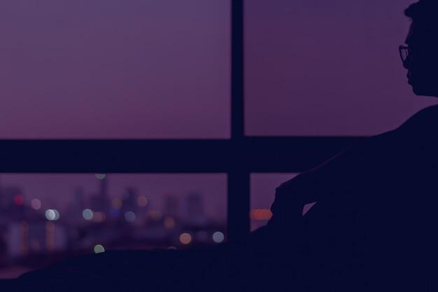 Homem sentado na cama sozinho à noite, olhando para fora