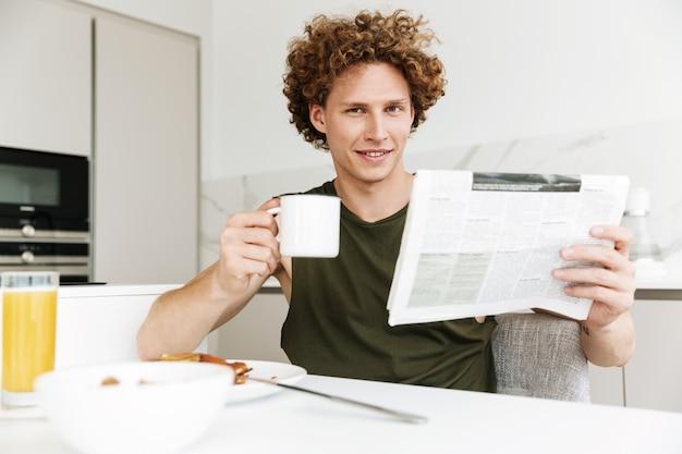Homem sentado na cozinha enquanto segura o jornal