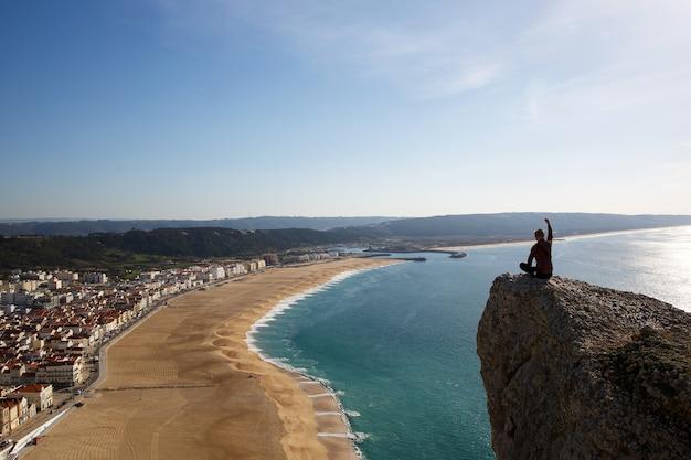 Homem sentado na falésia, olhando de cima para a praia do mar e uma pequena cidade