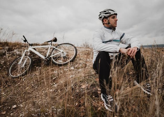 Homem sentado na grama ao lado de sua mountain bike