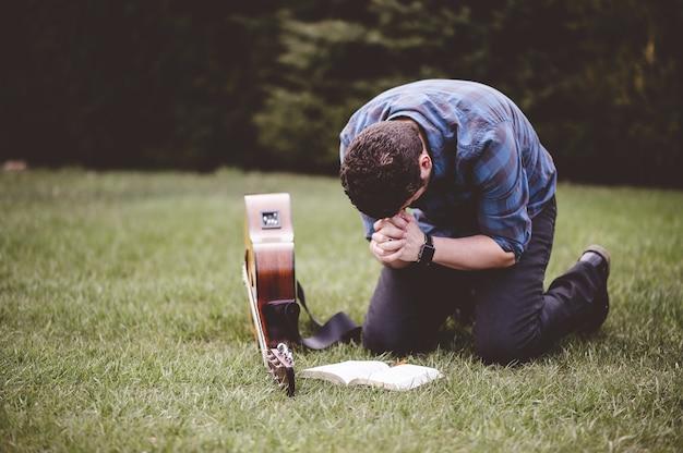 Homem sentado na grama e orando com um livro e um violão perto dele