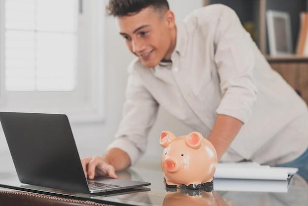 Homem sentado na mesa, gerenciar despesas, calcular despesas, pagar contas, laptop de uso on-line, fazer análise das finanças domésticas, fechar o foco no cofrinho rosa. economize dinheiro para o futuro, seja conceito previdente