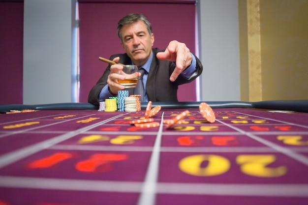 Homem sentado na mesa segurando um charuto jogando batatas fritas