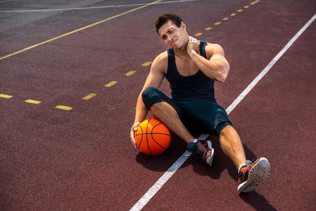 Homem sentado na quadra de basquete