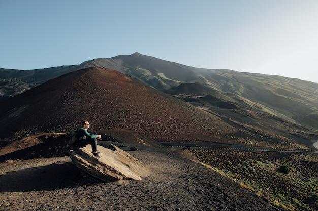 Homem sentado na rocha e apreciando a bela paisagem do vulcão etna, na sicília