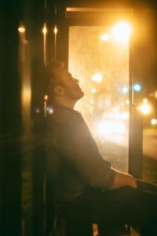 Homem sentado na rodoviária à noite na cidade