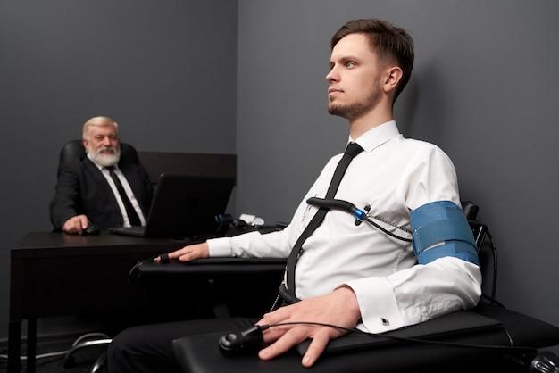 Homem sentado na sala cinza e verificando com o polígrafo.