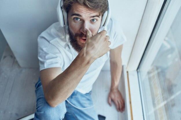 Homem sentado na sala com fones de ouvido se comunicando