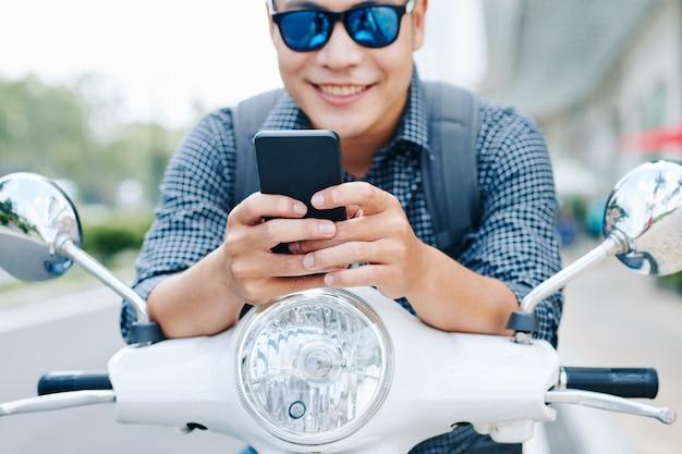 Homem sentado na scooter e mandando mensagens de texto
