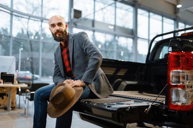 Homem sentado na traseira de um caminhão, concessionária de automóveis