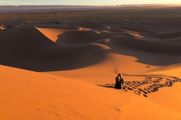 Homem sentado nas dunas de areia cercado por trilhas em um deserto
