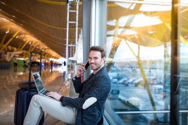 Homem sentado no aeroporto usando o laptop e telefone celular ao lado da janela