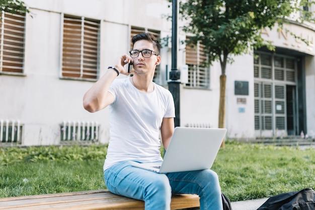 Homem sentado no banco com laptop falando no celular