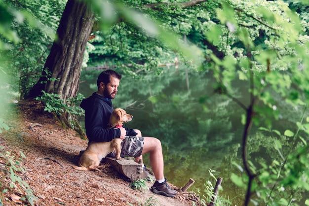 Homem sentado no banco com o cachorro à beira do lago