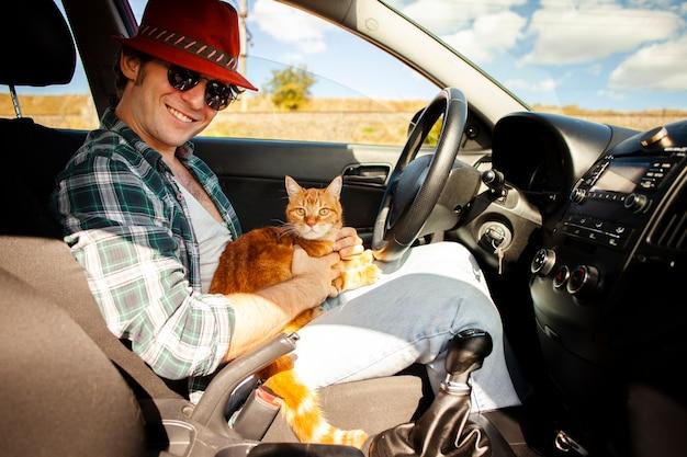 Homem sentado no banco do condutor com um gato