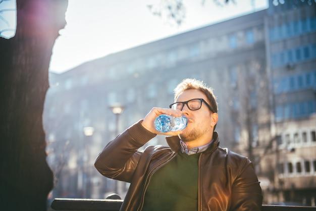 Homem sentado no banco do parque e água potável