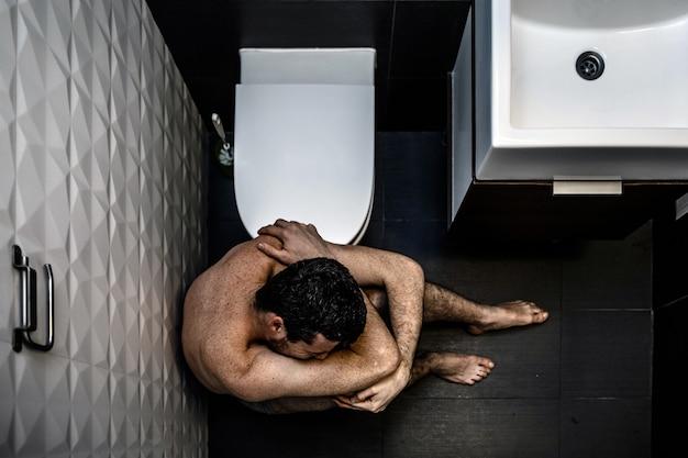 Homem sentado no banheiro