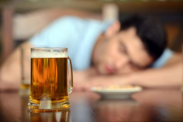Homem sentado no bar com os olhos fechados.