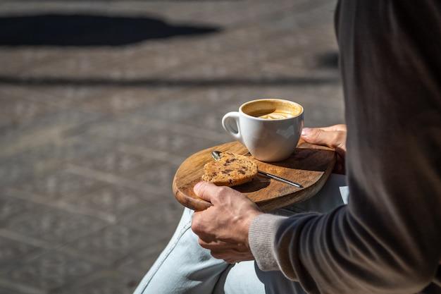 Homem sentado no café de rua com café e biscoito na bandeja de madeira