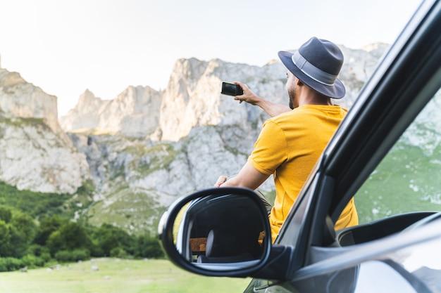 Homem sentado no capô do carro tirando foto para a montanha.