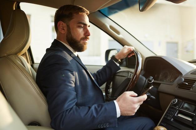 Homem sentado no carro de luxo