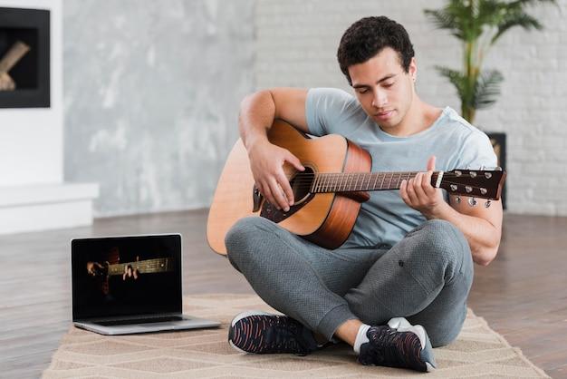 Homem sentado no chão aprendendo a tocar violão