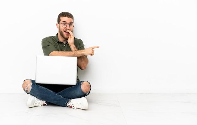 Homem sentado no chão com um laptop