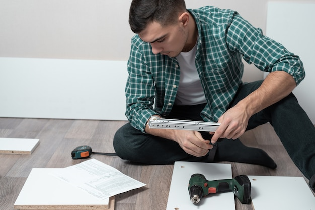 Homem sentado no chão da sala com ferramentas coletar móveis de acordo com as instruções