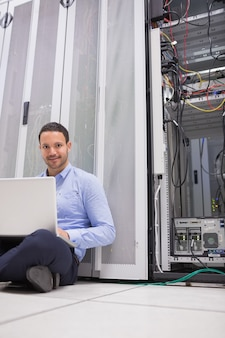 Homem sentado no chão usando laptop para verificar servidores