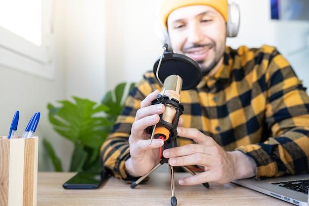 Homem sentado no escritório segurando um microfone com as mãos enquanto grava um programa de rádio