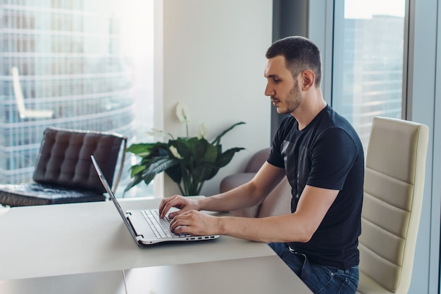 Homem sentado no local de trabalho e usando o laptop.