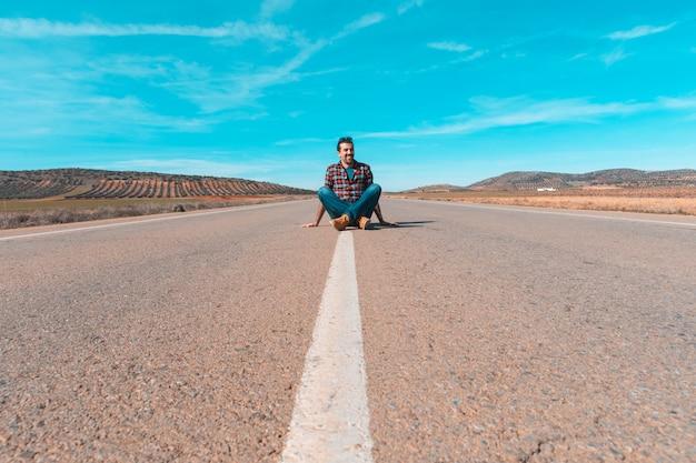 Homem sentado no meio de uma estrada reta vazia