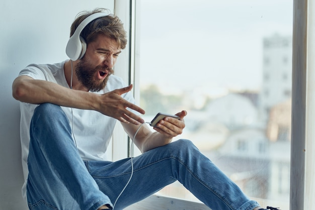 Homem sentado no parapeito da janela com fones de ouvido e descanso para fones de ouvido