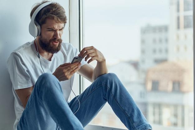 Homem sentado no parapeito da janela em fones de ouvido no estilo de vida de fones de ouvido