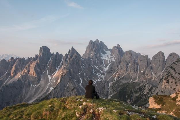 Homem sentado no penhasco de frente para a montanha cinza