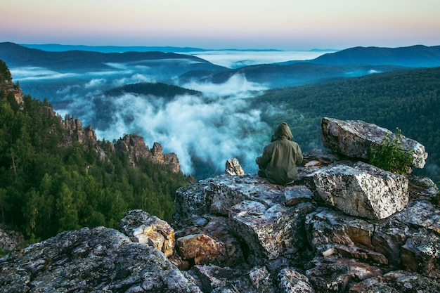 Homem sentado no pico das montanhas e aproveite para ver a bela paisagem de rochas e névoa chegando na manhã de verão
