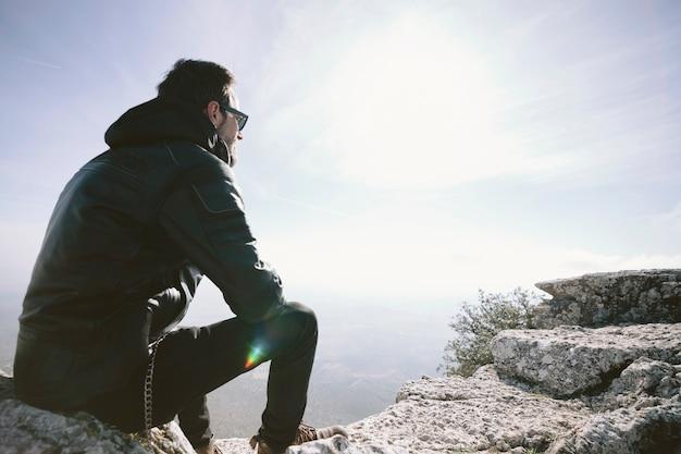 Homem sentado no rock