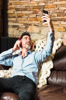 Homem sentado no sofá com fone de ouvido em suas orelhas, fazendo uma chamada de vídeo pelo smartphone