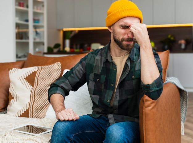 Homem sentado no sofá e com dor de cabeça