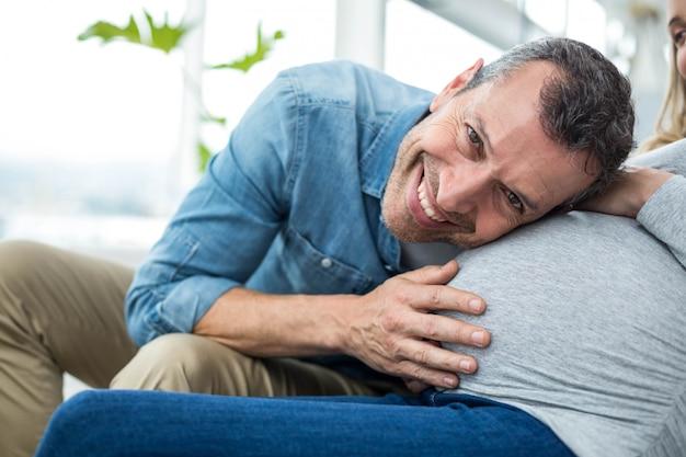 Homem sentado no sofá e ouvindo o estômago da mulher grávida