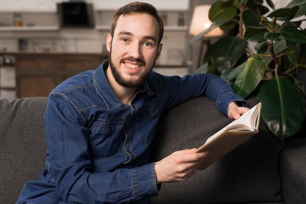 Homem sentado no sofá e segurando o livro