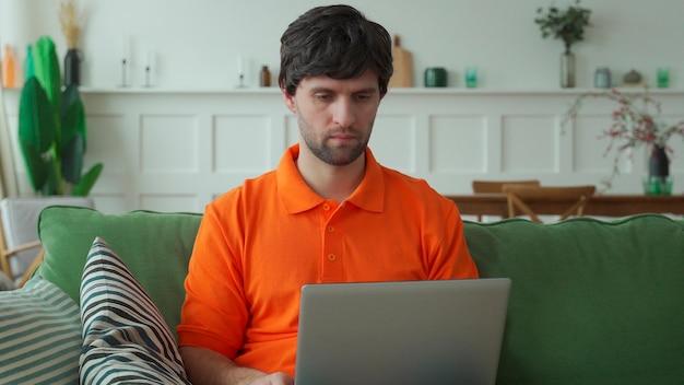 Homem sentado no sofá em casa usando um laptop