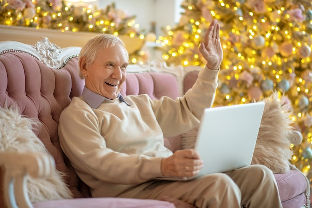 Homem sentado no sofá fazendo uma videochamada