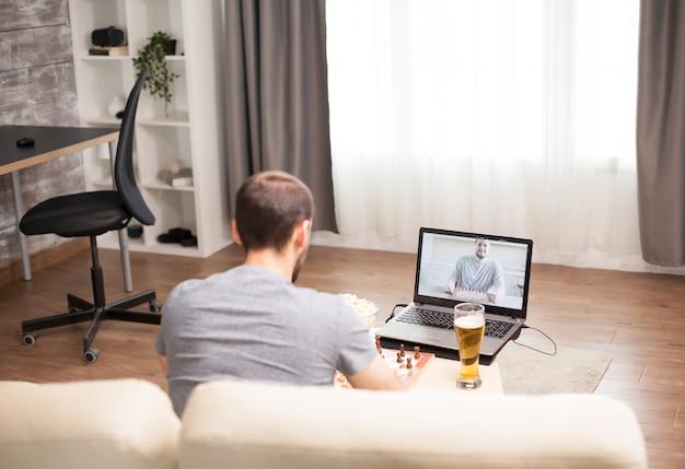 Homem sentado no sofá jogando xadrez com um amigo em uma videochamada durante a quarentena.