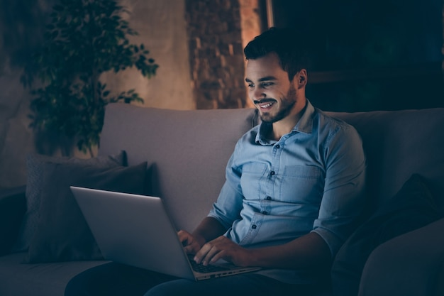Homem sentado no sofá trabalhando em um laptop