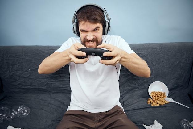 Homem sentado no sofá usando fones de ouvido com gamepad jogando comida, lazer, tecnologia, estilo de vida