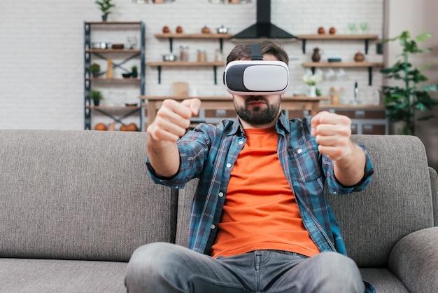Homem sentado no sofá usando óculos de realidade virtual, dirigindo o carro
