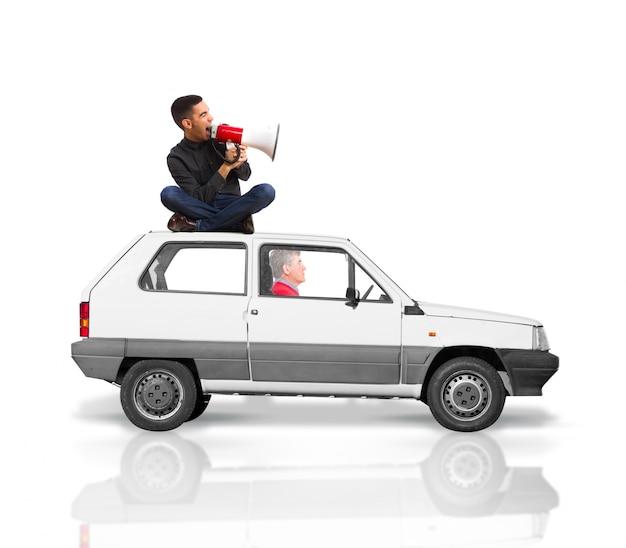 Homem sentado no telhado de um carro gritando por um megafone, enquanto um homem mais velho unidades