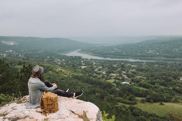 Homem sentado no topo da montanha com bela vista.