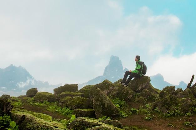 Homem sentado no topo de um cume rochoso ao fundo um céu de nuvens e nevoeiro